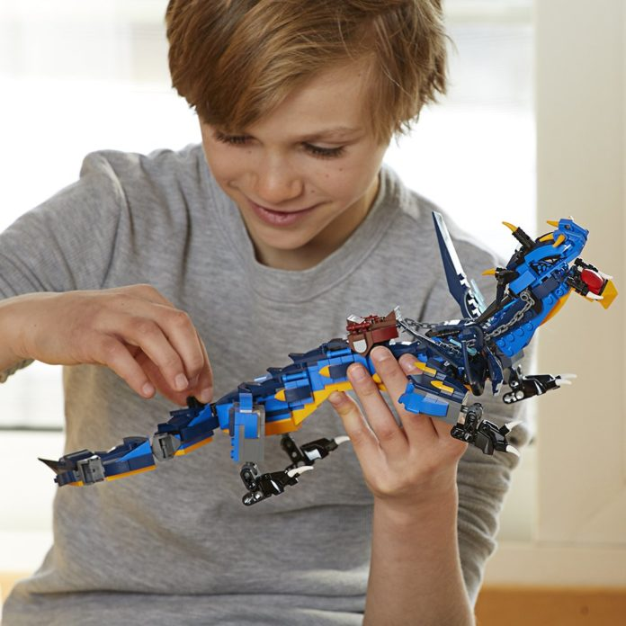 This is an image of a boy playing with a lego ninjango toy