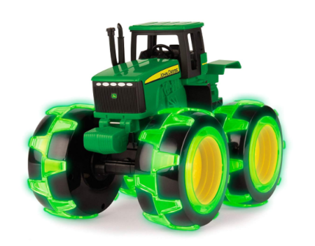 This is an image of a green tractor toy truck with wheel light.