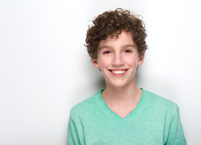 Close up portrait of a happy young 10 year old boy with curly hair smiling against white background